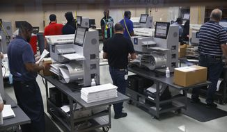Workers load ballots into machines at the Broward County Supervisor of Elections office during a recount on Sunday, Nov. 11, 2018, in Lauderhill, Fla. (AP Photo/Brynn Anderson)
