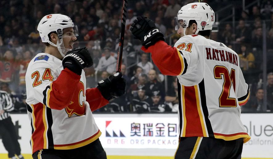 Calgary Flames defenseman Travis Hamonic, left, celebrates after scoring with right wing Garnet Hathaway during the first period of an NHL hockey game against the Los Angeles Kings in Los Angeles, Saturday, Nov. 10, 2018. (AP Photo/Chris Carlson)