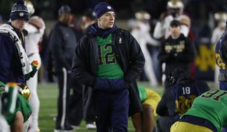 Notre Dame quarterback Ian Book (12) watches warmups before an NCAA college football game against Florida State in South Bend, Ind.,Saturday, Nov. 10, 2018. Book did not dress to play in the game. (AP Photo/Paul Sancya)
