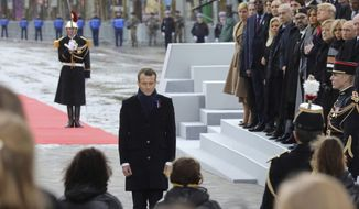 French President Emmanuel Macron pays his respects by the Tomb of the Unknown soldier during in a ceremony at the Arc de Triomphe in Paris, France, as part of the commemorations marking the 100th anniversary of the 11 November 1918 armistice, ending World War I, Sunday, Nov. 11, 2018. (Ludovic Marin/Pool Photo via AP)