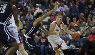 Virginia guard Kyle Guy (5) turns the corner past George Washington's Justin Mazzulla (0) in the first half of an NCAA college basketball game Sunday, Nov. 11, 2018, in Charlottesville, Va.  (Zack Wajsgras /The Daily Progress via AP)