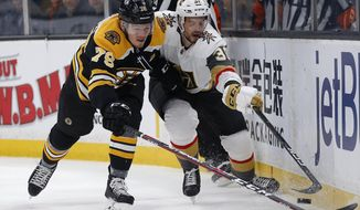 Boston Bruins' Jeremy Lauzon (79) and Vegas Golden Knights' Tomas Hyka (38) battle for the puck and during the first period of an NHL hockey game in Boston, Sunday, Nov. 11, 2018. (AP Photo/Michael Dwyer)
