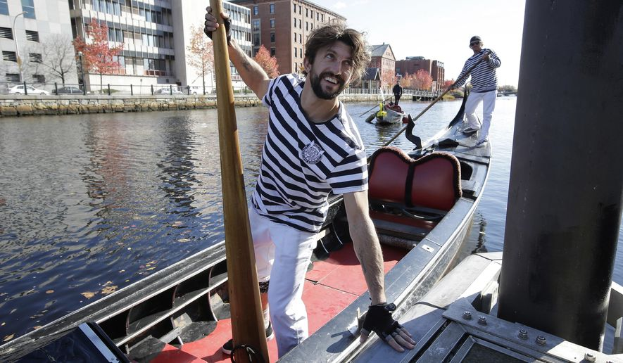 Michael Angelo Ruffino, of Huntington Beach, Calif., front, prepares to take part in the 2.6-mile tandem race in the U.S. Gondola Nationals, Sunday, Nov. 11, 2018, on the Providence River, in Providence, R.I. About 30 Venetian-style gondoliers from across the nation are competing in the U.S. Gondola Nationals that includes single and tandem races for sprint, distance and slalom courses. (AP Photo/Steven Senne)