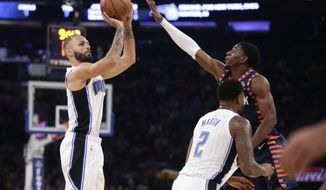 Orlando Magic's Evan Fournier, left, shoots over New York Knicks' Damyean Dotson during the first half of an NBA basketball game Sunday, Nov. 11, 2018, in New York. (AP Photo/Frank Franklin II)