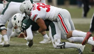 Michigan State quarterback Brian Lewerke (14) is sacked by Ohio State linebacker Tuf Borland (32) during the second half of an NCAA college football game, Saturday, Nov. 10, 2018, in East Lansing, Mich. (AP Photo/Carlos Osorio)