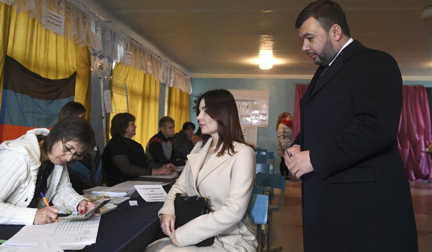Acting leader of the self-proclaimed Donetsk People's Republic Denis Pushilin, right, and his wife wait to get their ballots at a polling station during rebel elections in Donetsk, Ukraine, Sunday, Nov. 11, 2018. Residents of the eastern Ukraine regions controlled by Russia-backed separatist rebels are voting for local governments in elections denounced by Kiev and the West. (AP Photo)