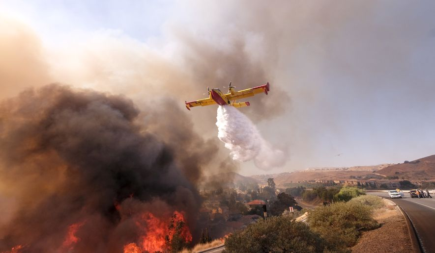 An air tanker drops water on a fire along the Ronald Reagan (118) Freeway in Simi Valley, Calif., Monday, Nov. 12, 2018. (AP Photo/Ringo H.W. Chiu)