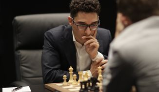 Italian-American challenger Fabiano Caruana plays reigning chess world champion Magnus Carlsen, right, from Norway, in round three of their World Chess Championship Match in London, Monday, Nov. 12, 2018. (AP Photo/Matt Dunham) ** FILE **