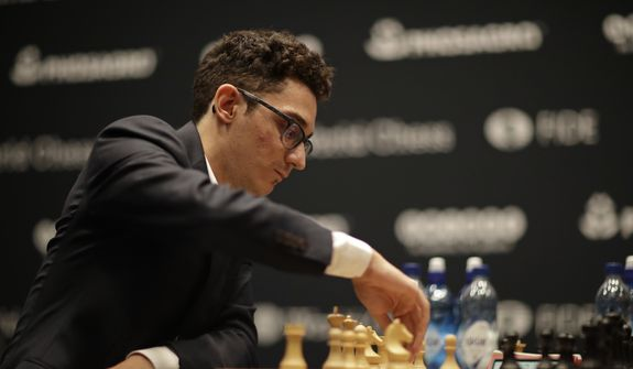 Italian-American challenger Fabiano Caruana plays reigning chess world champion Magnus Carlsen, not pictured, from Norway, in round three of their World Chess Championship Match in London, Monday, Nov. 12, 2018. Their World Chess Championship Match began on Friday in London. (AP Photo/Matt Dunham)