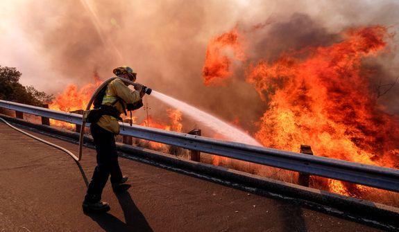 A firefighter battles a fire along the Ronald Reagan (118) Freeway in Simi Valley, Calif., Monday, Nov. 12, 2018. (AP Photo/Ringo H.W. Chiu)