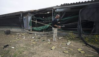 An Israeli security officer examines the damage of a chicken coop after it was hit by a rocket fired from southern Gaza Strip, Near the border with gaza southern Israel, Monday, Nov. 12, 2018. Israeli Prime Minister Benjamin Netanyahu rushed back to Israel on Monday, hours after an Israeli army officer and seven Palestinians, including a local Hamas commander, were killed after an incursion by Israeli special forces into the Gaza Strip. (APPhoto/Tsafrir Abayov)