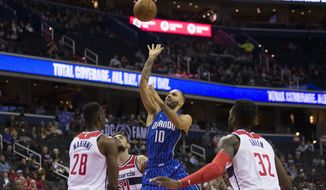 Orlando Magic guard Evan Fournier (10), from France, shoots between Washington Wizards center Ian Mahinmi (28), from France, guard Tomas Satoransky (31), from the Czech Republic, and forward Jeff Green (32) during the first half of an NBA basketball game Monday, Nov. 12, 2018, in Washington. (AP Photo/Alex Brandon)