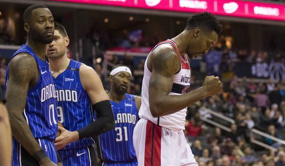 Washington Wizards center Dwight Howard, right, reacts after a foul as Orlando Magic forward Jonathon Simmons (17), center Nikola Vucevic (9), from Montenegro and guard Terrence Ross (31) stand nearby, during the second half of an NBA basketball game Monday, Nov. 12, 2018, in Washington. The Wizards won 117-109. (AP Photo/Alex Brandon) ** FILE **