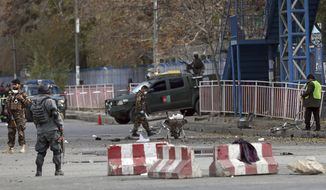 Security forces inspect the site of a deadly blast near a demonstration by hundreds of minority Shiites, in the center of Kabul, Afghanistan, Monday, Nov. 12, 2018. Afghan officials confirmed several people were killed in the explosion near a high school and about 500 meters (yards) from where people gathered to denounce Taliban attacks in Jaghuri and Malistan districts of eastern Ghazni province. (AP Photo/Massoud Hossaini)