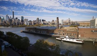 In this Wednesday, Nov. 7, 2018, photo, a rusting ferryboat is docked next to an aging industrial warehouse on Long Island City's Anable Basin in the Queens borough of New York. Across the East River is midtown Manhattan, top left. Long Island City is a longtime industrial and transportation hub that has become a fast-growing neighborhood of riverfront high-rises and redeveloped warehouses, with an enduring industrial foothold and burgeoning arts and tech scenes. (AP Photo/Mark Lennihan)