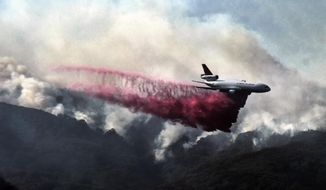 A firefighting DC-10 makes a fire retardant drop over a wildfire in the mountains near Malibu Canyon Road in Malibu, Calif. on Sunday, Nov. 11, 2018. Strong Santa Ana winds have returned to Southern California, fanning a huge wildfire that has scorched a string of communities west of Los Angeles. A one-day lull in the dry, northeasterly winds ended Sunday morning and authorities warn that the gusts will continue through Tuesday. (AP Photo/Richard Vogel)