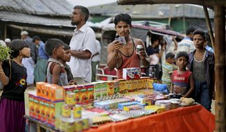 In this photograph taken Aug. 27, 2018, a Rohingya man looks at medicines being sold on the roadside in Balukhali refugee camp, Bangladesh. Faith healers have long been sought out in Rohingya society to treat physical and mental ailments. Their trade has thrived in part because of traditional beliefs and in part because Rohingya have lacked access to modern medical care in Buddhist-majority Myanmar, where they are one of the most persecuted minority groups in the world. Access to medical care has changed for the better in the refugee camps in Bangladesh, yet many Rohingya still seek out their faith healers. (AP Photo/Altaf Qadri)