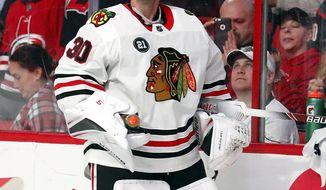 Chicago Blackhawks goaltender Cam Ward (30) watches the scoreboard as the Hurricanes' play a tribute video to their former long time goaltender during the first period of an NHL hockey game against the Carolina Hurricanes, Monday, Nov. 12, 2018, in Raleigh, N.C. (AP Photo/Karl B DeBlaker)