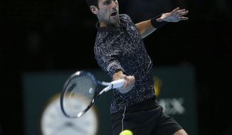Novak Djokovic of Serbia plays a return to John Isner of the United States in their ATP World Tour Finals doubles tennis match at the O2 Arena in London, Monday Nov. 12, 2018. (AP Photo/Tim Ireland)