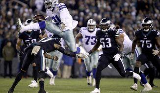 Dallas Cowboys running back Ezekiel Elliott (21) hurdles over Philadelphia Eagles defensive back Tre Sullivan (37) during the first half of an NFL football game, Sunday, Nov. 11, 2018, in Philadelphia. (AP Photo/Matt Rourke)