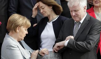FILE - In this April 10, 2018 file photo German Chancellor Angela Merkel, left, and German Interior Minister Horst Seehofer, right, look at their watches after they and other members of the government posed for a group photo during two-day retreat at the government guest house Meseberg castle in Gransee north of Berlin, Germany. In the center is German Justice Minister Katarina Barley. Germany's top security official, who has frequently criticized Chancellor Angela Merkel's migrant policy, is reportedly planning to quit his post in government.German news agency dpa quoted multiple unnamed party officials as saying Horst Seehofer told a meeting of the Christian Social Union on Sunday that he plans to relinquish its leadership and his role as interior minister in Merkel's government.  (AP Photo/Michael Sohn, file)