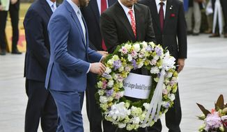 Mitch Haniger of the Seattle Mariners, front left, Kenta Maeda, of the Los Angeles Dodgers, front right, with manager Don Mattingly, rear left, lay a wreath at the cenotaph in the Peace Memorial Park which commemorates the victims of the atomic bombings in 1945, in Hiroshima, western Japan, Monday, Nov. 12, 2018. (Kyodo News via AP)