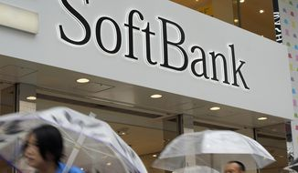 In this June 15, 2018, file photo, people walk under the logo of Japanese internet company SoftBank Corp. at its mobile phone shop in Tokyo. Japanese technology company SoftBank Group Corp. will carry out an initial public offering of its Japanese mobile subsidiary, set for Dec. 19. (AP Photo/Shuji Kajiyama, File)