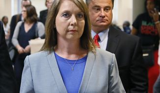 FILE - In this Wednesday, May 17, 2017 file photo, Betty Shelby leaves the courtroom with her husband, Dave Shelby, right, after the jury in her case began deliberations in Tulsa, Okla. The Oklahoma deputy acquitted in a 2016 fatal shooting of an unarmed black man is no longer scheduled to speak at a homicide investigators conference in Baton Rouge, Louisiana.News outlets report the Southeastern Homicide Investigators Association rescinded Roger County Sheriff's Deputy Betty Shelby's invitation on Sunday, Nov. 11, 2018, following pressure from civil rights leaders. Shelby is a former Tulsa police officer charged and acquitted of manslaughter in the killing of Terence Crutcher. She later resigned.(AP Photo/Sue Ogrocki, File)