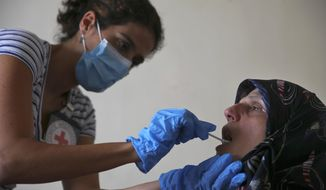 FILE - This Monday, July 11, 2016 file photo, a member of The International Red Cross takes a saliva sample from Umalbaneen Ali Wehbe, sister of Habib Ali Wehbe who went missing in 1976 during the Lebanese civil war, at her home, in the southern suburb of Beirut Beirut, Lebanon. Lebanon's parliament approved Monday, Nov. 12, 2018 the formation of an independent commission to help determine the fate of thousands of people who went missing during the country's civil war 28 years after it ended. (AP Photo/Hassan Ammar, File)