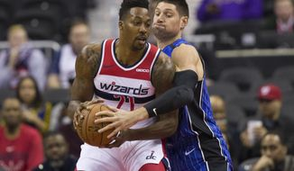 Washington Wizards center Dwight Howard (21) hangs onto the ball as Orlando Magic center Nikola Vucevic, from Montenegro, reaches for it during the first half of an NBA basketball game Monday, Nov. 12, 2018, in Washington. (AP Photo/Alex Brandon)