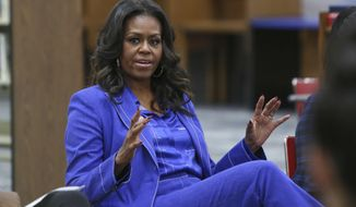 """Former first lady Michelle Obama speaks with students at her alma mater, Whitney M. Young Magnet High School, on Chicago's West Side, Monday, Nov. 12, 2018, a day before the launch of a book tour to promote her memoir, """"Becoming."""" (AP Photo/Teresa Crawford)"""