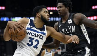 Brooklyn Nets' Ed Davis (17) guards Minnesota Timberwolves' Karl-Anthony Towns (32) during the fourth quarter of an NBA basketball game on Monday, Nov. 12, 2018, in Minneapolis. The Timberwolves won 120-113. (AP Photo/Hannah Foslien)