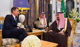 In this photo released by Saudi Press Agency, Saudi King Salman, right, talks to the UK's foreign secretary Jeremy Hunt, in Riyadh, Monday, Nov. 12, 2018. Hunt was expected to press the kingdom to fully cooperate with a Turkish investigation into last month's killing of Saudi writer Jamal Khashoggi at the kingdom's consulate in Istanbul. The foreign secretary is the first British minister to visit Saudi Arabia since Khashoggi was killed by what Ankara has said was an assassination squad sent for the dissident writer. (Saudi Press Agency via AP)