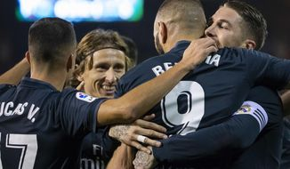 Real Madrid's Karim Benzema is congratulated by teammates after scoring a goal during a Spanish La Liga soccer match between RC Celta and Real Madrid at the Balaidos stadium in Vigo, Spain, Sunday, November 11, 2018. (AP Photo/Lalo R. Villar)