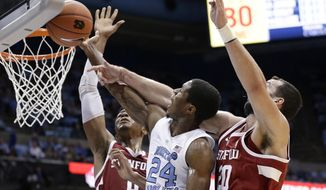 North Carolina's Kenny Williams (24) drives to the basket while Stanford's Josh Sharma (20) and KZ Okpala defend during the first half of an NCAA college basketball game in Chapel Hill, N.C., Monday, Nov. 12, 2018. (AP Photo/Gerry Broome)