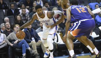 Oklahoma City Thunder forward Paul George (13) tries to push past Phoenix Suns forward Trevor Ariza (3) and T.J. Warren (12) in the second half of an NBA basketball game in Oklahoma City, Monday, Nov. 12, 2018. (AP Photo/Kyle Phillips)