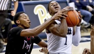 Troy's Javan Johnson, left, grabs Pittsburgh's Xavier Johnson as he shoots during the first half of an NCAA college basketball game, Monday, Nov. 12, 2018, in Pittsburgh. (AP Photo/Keith Srakocic)