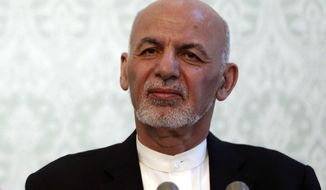 FILE - IN this Nov. 6, 2018, photo, Afghan President Ashraf Ghani, listens during a news conference with NATO Secretary General Jens Stoltenberg, at the presidential palace, in Kabul, Afghanistan. Ghani is denying the Taliban is winning the war in Afghanistan despite a continuing wave of deadly militant attacks and signs the militants are expanding areas under their control. Ghani said the Afghan state is not at risk of collapse and reiterated his government's intent to seek a negotiated peace. Ghani was speaking by video to an audience in Washington. (AP Photo/Massoud Hossaini)