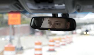 In a photo taken Friday, Nov. 9, 2018, in Staten Island, Lenny Sciascia is seen in the rearview mirror of his vehicle as he drives to New Jersey, where online betting is legal, to place bets on sporting events from his smartphone. With sports betting being advertised all around them but the opportunity to actually do it restricted to just one nearby state, gamblers from New York and Pennsylvania are crossing bridges and tunnels into New Jersey to make legal sports bets. (AP Photo/Julio Cortez)