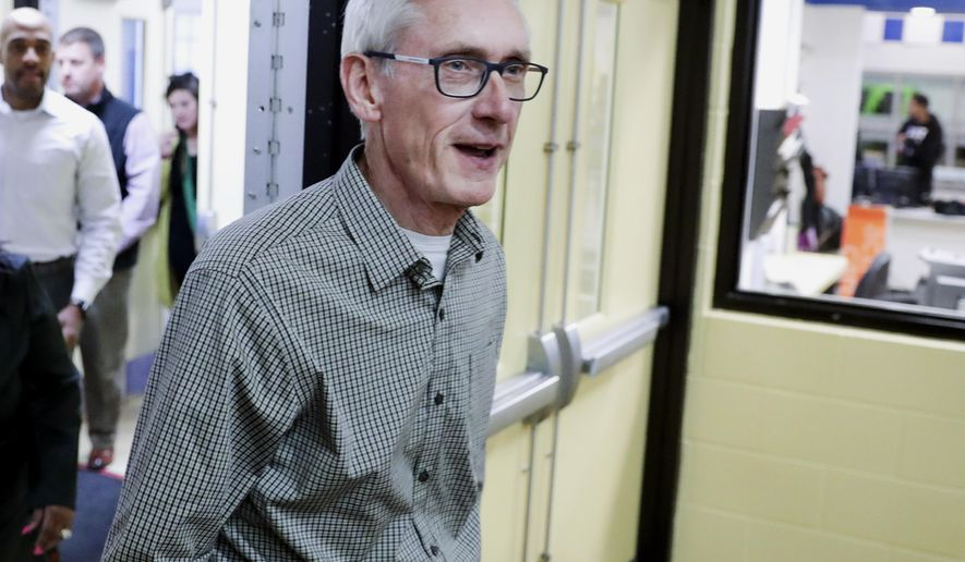 FILE - In this Nov. 7, 2018, file photo, Wisconsin Democratic Gov.-elect Tony Evers walks into a room before speaking with reporters in Madison, Wis. Evers named his transition team Monday, Nov. 12, 2018, as Republicans who control the Legislature continued to privately discuss ways to curtail the new governor's power before he takes office in less than two months. (Steve Apps/Wisconsin State Journal via AP, File)