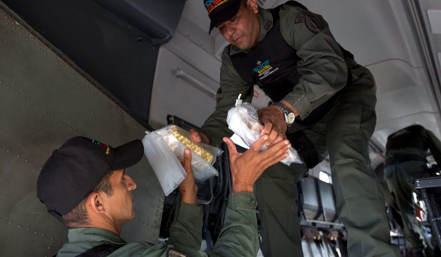 Members of a military agency that transports valuables remove gold bars from a military plane to be taken to Venezuela's Central Bank, at the Carlota military airport in Caracas, Venezuela, Thursday, March 1, 2018. Since January, Venezuela's central bank has accumulated 3.7 tons of gold from the Orinoco mining belt in southern Bolivar state, which is almost half of the 8.5 tons dispatched in all of 2017. (AP Photo/Ariana Cubillos)