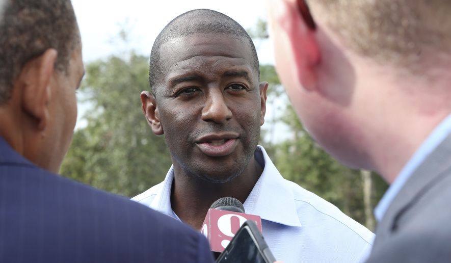 Tallahassee Mayor Andrew Gillum talks with reporters after a campaign stop in his bid for governor, Monday, Nov. 5, 2018, in Crawfordville, Fla. (AP Photo/Steve Cannon)