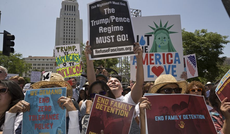 In this June 30, 2018, file photo, protesters gather to demonstrate against President Donald Trump's immigration policies in downtown Los Angeles. (AP Photo/Damian Dovarganes, File)