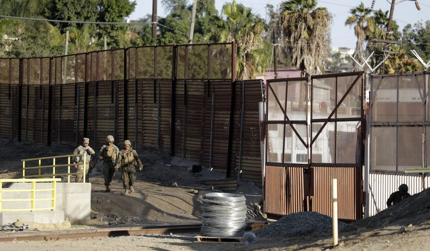 Marines patrol during work to fortify the border structure that separates Tijuana, Mexico, behind, and San Diego, near the San Ysidro Port of Entry, Friday, Nov. 9, 2018, in San Diego. The military along the California border with Mexico worked Friday to fortify the border structure, including adding concertina wire to the tops of the rusting wall of corrugated metal. The military is expected to have the vast majority of the more than 7,000 troops planned for the border-wide mission deployed by Monday, and that number could grow. (AP Photo/Gregory Bull)