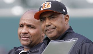 FILE - In this June 3, 2014, file photo, Cincinnati Bengals head coach Marvin Lewis, right, talks with then-offensive coordinator Hue Jackson during an NFL football organized team activity,  in Cincinnati. Jackson needed only a few weeks to land another job in the place where he's always welcomed. The Bengals hired Jackson on Tuesday, Nov. 13, 2018,  as a special assistant to head coach Marvin Lewis as he tries to resurrect Cincinnati's historically bad defense. Jackson was fired by the Cleveland Browns last month after he won only three games in three seasons as head coach.(AP Photo/Al Behrman) ** FILE **