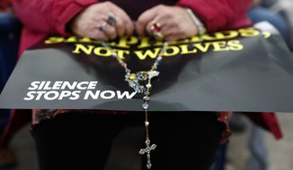 A woman prays the rosary at a rally organized by a coalition of conservative Catholic groups near the United States Conference of Catholic Bishops' annual fall meeting, Tuesday, Nov. 13, 2018, in Baltimore. (AP Photo/Patrick Semansky)