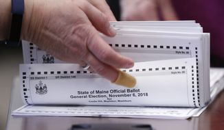 In this Nov. 12, 2018, file photo, ballots are prepared to be tabulated for Maine's 2nd Congressional District's House election in Augusta. Republican U.S. Rep. Bruce Poliquin and three voters sued Tuesday, Nov. 13, over Maine's new voting system, used for the first time in U.S. House and Senate elections. A lawyer for Poliquin's campaign asked the secretary of state to stop the tabulations to allow a judge to rule, but the secretary declined to stop the process. (AP Photo/Robert F. Bukaty, File)