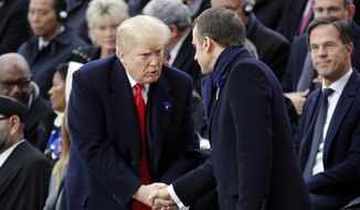 U.S President Donald Trump, left, shakes hands with French President Emmanuel Macron during ceremonies at the Arc de Triomphe Sunday, Nov. 11, 2018 in Paris. Over 60 heads of state and government were taking part in a solemn ceremony at the Tomb of the Unknown Soldier, the mute and powerful symbol of sacrifice to the millions who died from 1914-18. (AP Photo/Francois Mori, Pool)