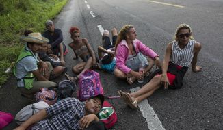 In this Nov. 2, 2018 photo, members of the LGBTQ community who are traveling with the Central American migrants caravan hoping to reach the U.S. border, wait on the side of the road for a ride to Donaji, Mexico. Fearful of being attacked violently or sexually assaulted, they've stuck by each other's side 24 hours a day, walking and sleeping in a group. (AP Photo/Rodrigo Abd)