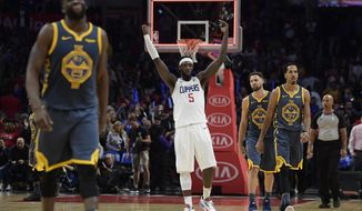 Los Angeles Clippers forward Montrezl Harrell, center, celebrates as time runs out in overtime as Golden State Warriors forward Draymond Green, left, guard Klay Thompson, second from right, and guard Shaun Livingston walk off the court in an NBA basketball game, Monday, Nov. 12, 2018, in Los Angeles. The Clippers won 121-116 in overtime. (AP Photo/Mark J. Terrill)